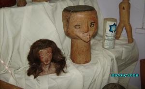 Esquerda para a direita: Cabeça feminina esculpida em madeira, com representação de sobrancelhas, olhos nariz e boca, compondo a face. possui também uma peruca com cabelos naturais. cabeça masculina, esculpida em amdeira, com a parte superior da cabeça achatada, pintada de preto, simulnado cabelos. Possui nariz, boca e orelhas esculpidos, mas os olhos são pintados sobra a face.