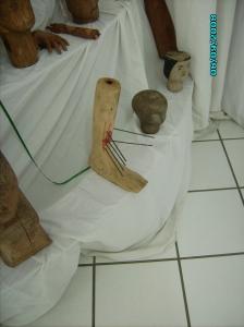 Perna humana, esculpida em madeira, com seis hastes de metal inseridas na altura do tornozelo, com pintura vermelha simulando sangue. Representa um provável ferimento, que teria sido o motivo da confecção do ex-voto.